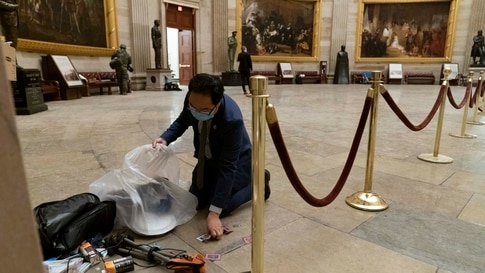 Rep. Andy Kim, D-N.J., cleans up debris and personal belongings strewn across the floor of the Rotunda in the early morning…