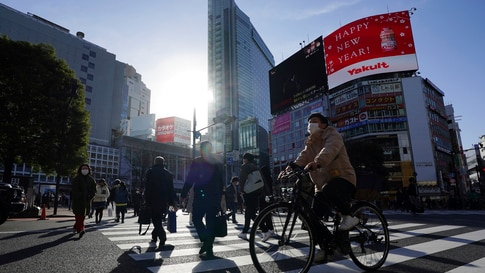 People wearing protective masks to help curb the spread of the coronavirus walk along pedestrian crossings in the Shibuya area…