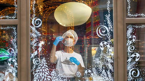 A cook in a face mask is seen making a pizza through a window glass decorated with Christmas ornaments in a city pizzeria in…