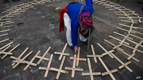 A Mayan spiritual guide arranges crosses, marked with the names of people who died in the nation's civil war, in a circle in…