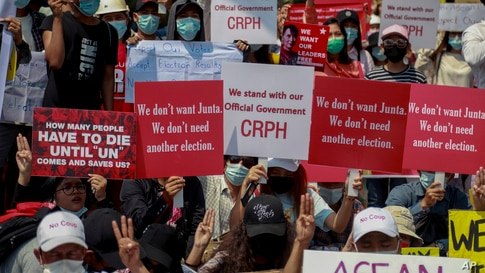 Demonstrators display placards during a protest close to Indonesian Embassy in Yangon, Myanmar Tuesday, Feb. 23, 2021. Anti…