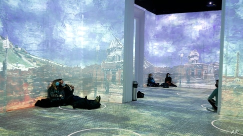Patrons socially distance in different rooms as they look at the moving images cast on the walls and floors during a virtual…