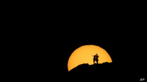 Two hikers are silhouetted against the setting sun at Papago Park in Phoenix, Sunday, Feb. 21, 2021. (AP Photo/Jae C. Hong)