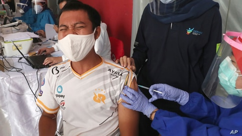 A man reacts as he receives a shot of COVID-19 vaccine during a mass vaccination for traders and workers at Tanah Abang Market…