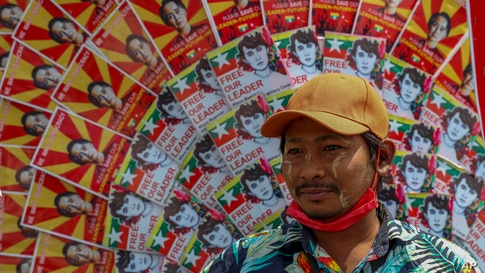 An anti-coup protester stands next to images of deposed Myanmar leader Aung San Suu Kyi during a street march in Mandalay,…