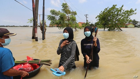 Indonesians carry their belongings as they wade through the water in a flooded neighborhood following heavy rains in Bekasi,…