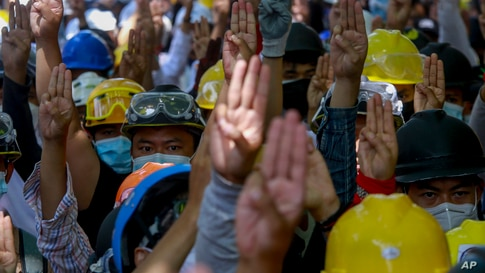 Anti-coup protesters flash a three-fingered sign of resistance during a demonstration in Yangon, Myanmar, Thursday, March 4,…