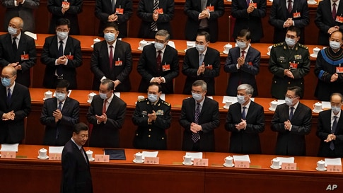 Delegates wearing face masks to help curb the spread of the coronavirus applaud as Chinese President Xi Jinping arrives for the…