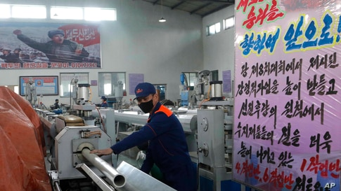 An employee of the Rangnang Disabled Soldiers' Essential Plastic Goods Factory checks the quality of a plastic pipe in…