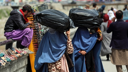 Women carry sacks of goods in a street market in Kabul, Afghanistan, Wednesday, April 7, 2021. (AP Photo/Rahmat Gul)