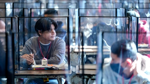 Students sit separated by plastic dividers during lunch at Wyandotte County High School in Kansas City, Kan. on the first day…