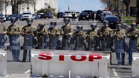 Troops stand guard near the scene of a car that crashed into a barrier on Capitol Hill in Washington, Friday, April 2, 2021. …
