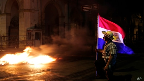 A man carries a Paraguayan flag during a protest in front of the Congress building, asking for the resignation of President…