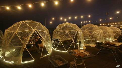 People enjoy outdoor dining at plastic bubbles, observing social distancing against the spread of the coronavirus at a…
