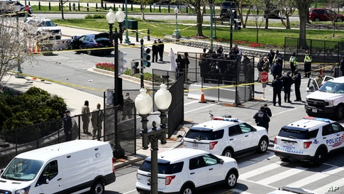Police officers gather near a car that crashed into a barrier on Capitol Hill in Washington, Friday, April 2, 2021. (AP Photo/J…