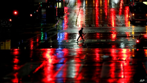 A man crosses Corrientes Avenue in Buenos Aires, Argentina, early Friday, April 9, 2021. Argentina has issued a nighttime…