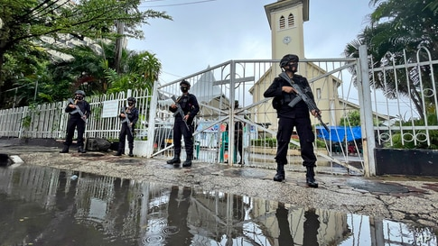 Armed police officers stand guard at the gate of the Sacred Heart of Jesus Cathedral which was attacked by suicide bomb on…