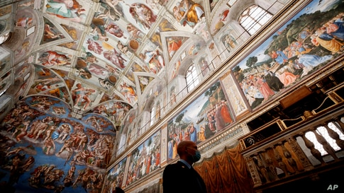 A museum employee wears a face mask to curb the spread of COVID-19 as he walks inside the Sistine Chapel of the Vatican Museums…