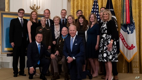 President Joe Biden takes a knee for a group photo with South Korean President Moon Jae-in, kneeling left, after presenting the…