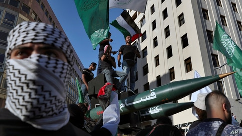 Palestinians living in Lebanon carry replica rockets during a march in support of Palestinians, in Beirut, Lebanon, Tuesday,…