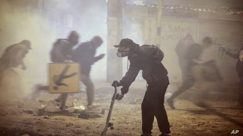 Anti-government protesters run during clashes with the police in Bogota, Colombia, Wednesday, May 26, 2021. Colombians have…