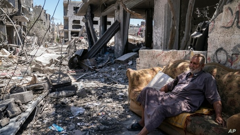 Mofeed Sabit, 64, sits on a couch along a road covered in debris, from an airstrike that destroyed a building prior to a cease…