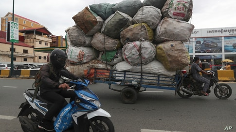 A woman, right, transports huge bags of recyclables on a street, in downtown Phnom Penh, Cambodia, Monday, May 24, 2021. (AP…