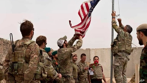 A U.S. flag is lowered as American and Afghan soldiers attend a handover ceremony from the U.S. Army to the Afghan National…