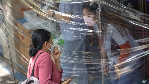 A customer wearing a protective mask to help curb the spread of the coronavirus orders medicine through plastic sheets in front…