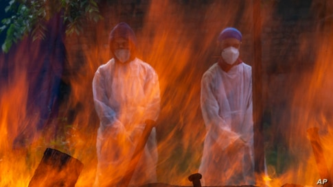 Relatives in protective suits stand next to the burning pyre of a person who died of COVID-19, at a crematorium in Srinagar,…