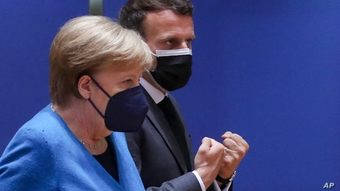 German Chancellor Angela Merkel, left, speaks with French President Emmanuel Macron during a round table meeting at an EU…