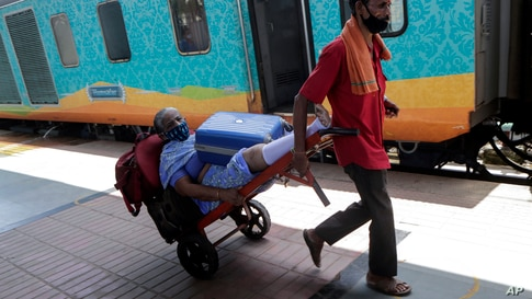 A railway porter transports on a baggage trolley an elderly passenger who has difficulties in walking as she assists her board…