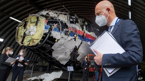 Presiding judge Hendrik Steenhuis, right, and other trial judges and lawyers view the reconstructed wreckage of Malaysia…