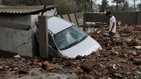 A man looks at a car damaged due to Cyclone Yaas that made a landfall Wednesday at Digha on the Bay of Bengal coast, West…