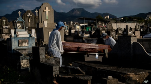 Cemetery workers carry the coffin that contains the remains of 89-year-old Irodina Pinto Ribeiro, who died from COVID-19…