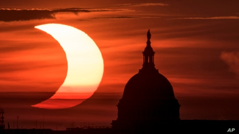 In this photo provided by NASA, a partial solar eclipse is seen as the sun rises to the left of the U.S. Capitol in Washington,…