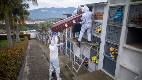 Cemetery and funeral workers place the coffin of a man who died of COVID-19 into a niche at the Nuestra Señora de Belen…