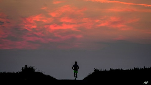 A man runs on a small road in the outskirts of Frankfurt, Germany, before sunrise on Wednesday, June 9, 2021. (AP Photo/Michael…