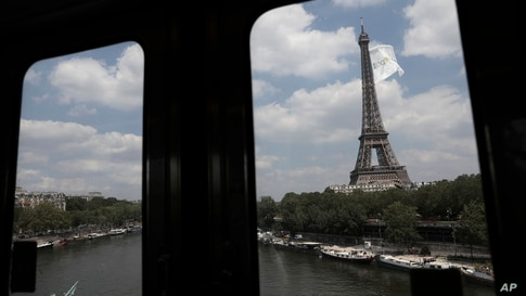 Pictured from the elevated subway train, a giant flag flies at the Eiffel Tower in Paris, Tuesday, June 8, 2021. The reason of…