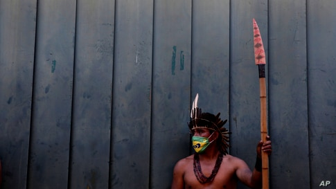 An Indigenous man wearing a protective face mask amid the COVID-19 pandemic takes part in a protest against Brazilian President…