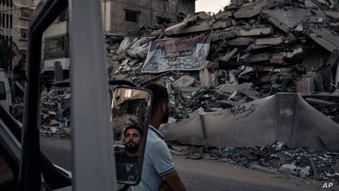 Palestinians look at the rubble of a building that collapsed after it was hit by airstrikes during an 11-day war between Gaza's…