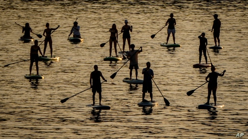 Stand up paddlers ride their boards on the river Main in Frankfurt, Germany, on a hot Friday evening, June 18, 2021. (AP Photo…