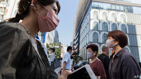 People wearing face masks walk across an intersection in the Ginza shopping district in Tokyo on Thursday, June 10, 2021. (AP…