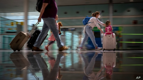 Tourists arrive at Barcelona airport, Spain, Monday, June 7, 2021. Spain is trying to ramp up its tourism industry by welcoming…