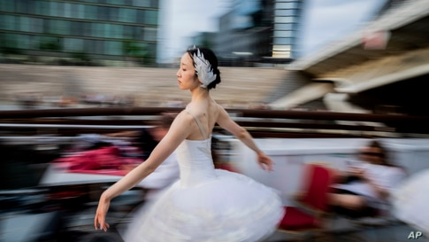 """A dancer from the Berlin State Ballet dances """"Swan Lake"""" on an excursion boat during a tour of the city centre, in Berlin,…"""