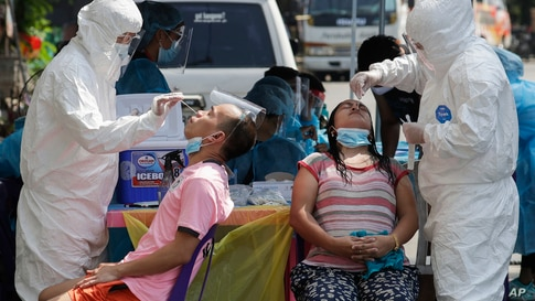 Health workers conduct a COVID-19 swab test on residents as they monitor cases at a village in Quezon City, Philippines on…