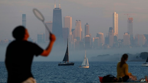People play and spend time along the shore of Lake Michigan as evening fog covers the downtown skyline, Wednesday, June 9, 2021…