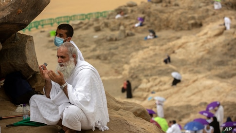 A Muslim pilgrim prays on top of the rocky hill known as the Mountain of Mercy, on the Plain of Arafat, during the annual hajj…