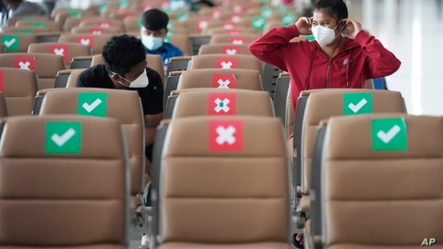 Passengers sit spaced apart while wearing face masks to help curb the spread of the coronavirus at Suvarnabhumi airport in…