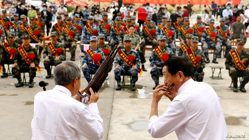 Performers play musical instruments at a ceremony to welcome new recruits of Chinese PLA, in Shijiazhuang